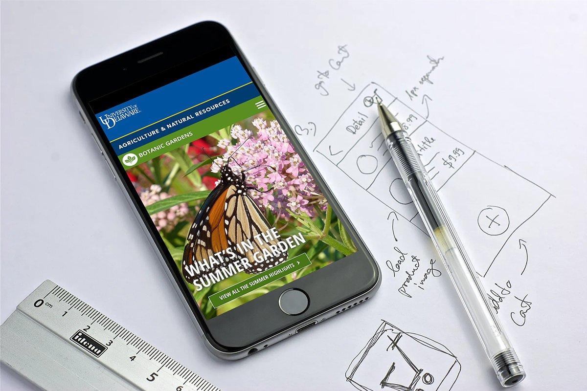 A phone showing the Blue Blaze designed University of Delaware Botanic Gardens website