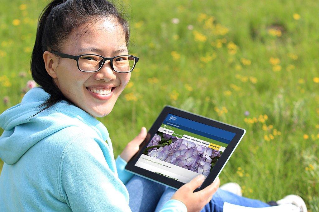 A tablet showing the Blue Blaze designed University of Delaware Botanic Gardens website