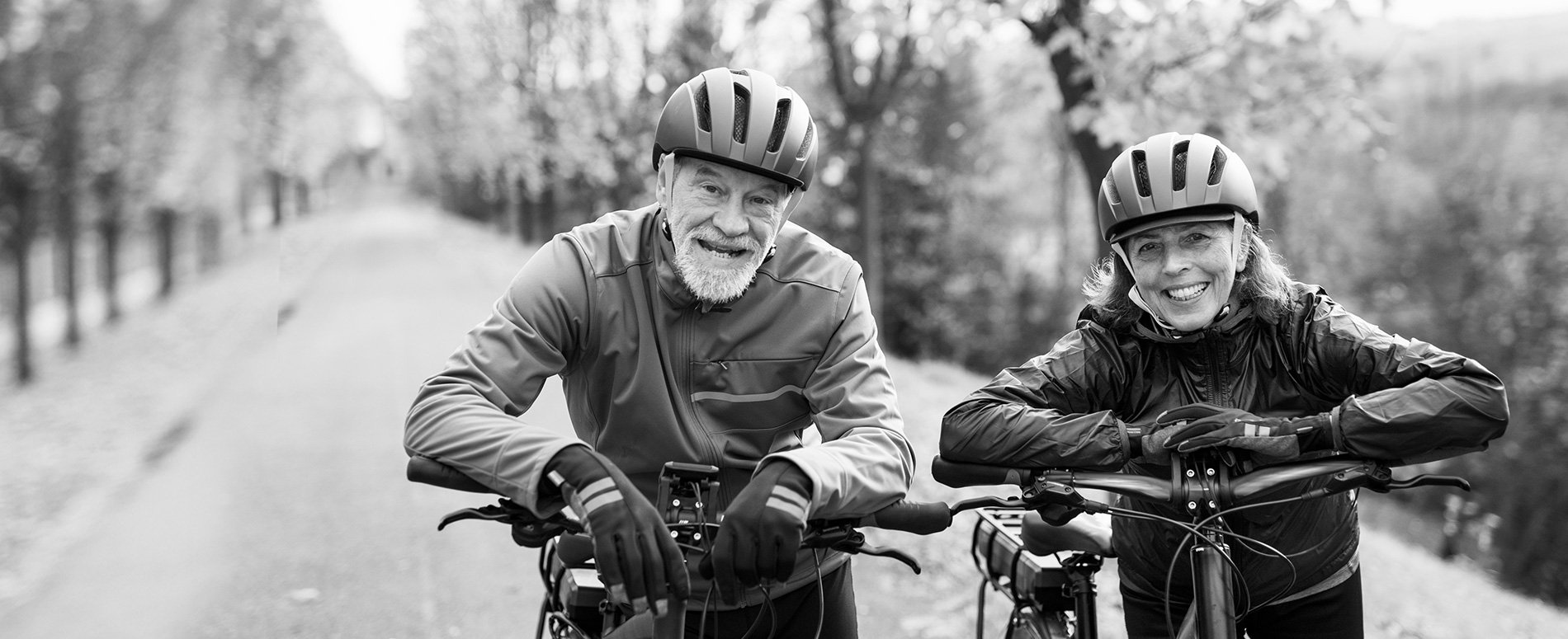 Senior couple smiling while on bicycles outdoors.